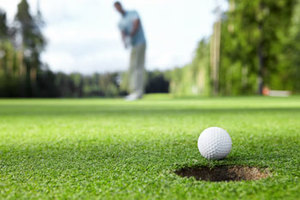 Closeup of a golfer making a putt in a hole